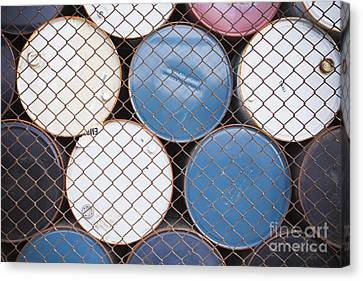 Rows Of Stacked Barrels Behind A Fence Canvas Print by Paul Edmondson