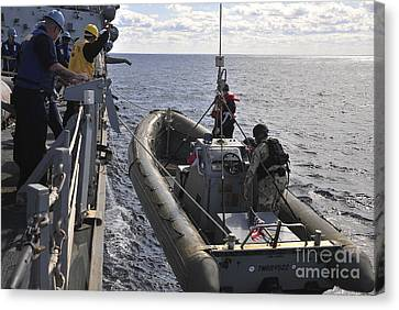 Sailors Lift A Rigid-hull Inflatable Canvas Print by Stocktrek Images