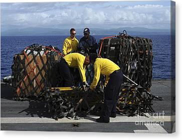 Sailors Prepare Pallets Of Cargo Aboard Canvas Print by Stocktrek Images