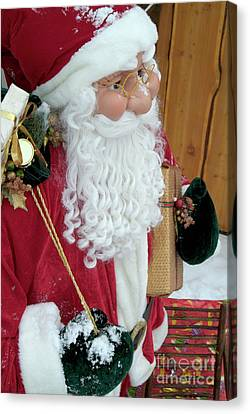 Santa Claus Toy Standing Next To Christmas Presents Canvas Print by Sami Sarkis