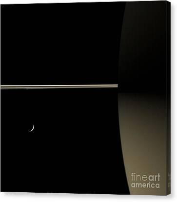 Saturn And Its Moon Tethys Canvas Print by NASA/Science Source