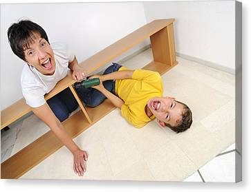 Screaming Mother And Son Assembling Furniture Canvas Print by Matthias Hauser