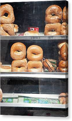 Selection Of Bagels On Shelves Behind A Shop Window Canvas Print by Paul Hudson