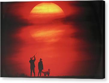 Silhouette Of Couple With Dog, Man Aiming, Sunset Canvas Print by David De Lossy
