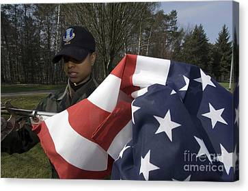 Soldier Unfurls A New Flag For Posting Canvas Print by Stocktrek Images