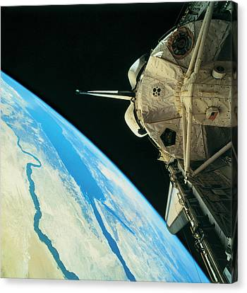 Space Shuttle Orbiting The Earth Canvas Print