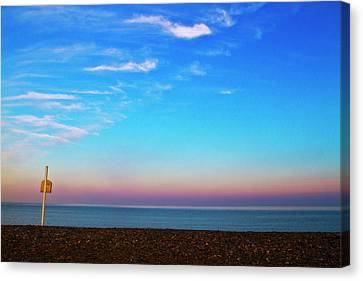 Sunset On Empty Beach With Lifebouy On Post Canvas Print by Image by Catherine MacBride