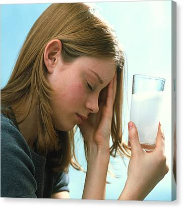 Teenager With Headache Holds Dissolving Painkiller Canvas Print by Damien Lovegrove
