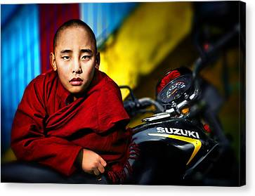 The Boy Monk In Red Robe Standing Beside A Motorcycle In A Buddh Canvas Print by Max Drukpa