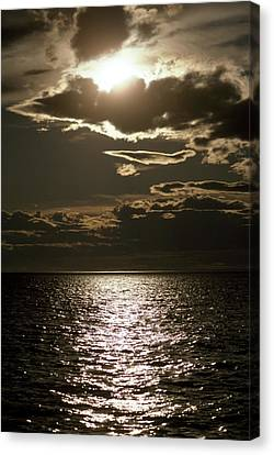 The Setting Sun Pierces A Menacing Canvas Print by Jason Edwards