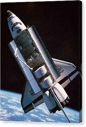 The Space Shuttle With Cargo Bay Open Orbiting Above Earth Canvas Print by Stockbyte