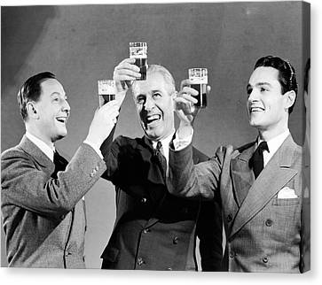 Three Men Making Toast With Glasses Of Beer (b&w) Canvas Print by Hulton Archive
