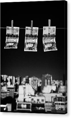 Three Twenty Pounds Sterling Banknotes Hanging On A Washing Line With Blue Sky Above A City Skyline Canvas Print by Joe Fox