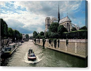 Canvas Print featuring the photograph Tour Boat Passing Notre Dame by Dave Mills