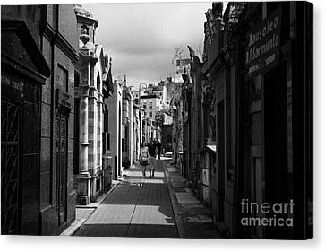 Tourists Walk Row Of Older Mausoleums On A Street In Recoleta Cemetery Capital Federal Buenos Aires Canvas Print by Joe Fox