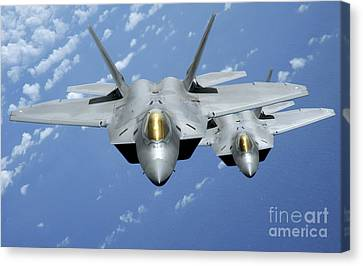 Two F-22 Raptors Fly Over The Pacific Canvas Print by Stocktrek Images