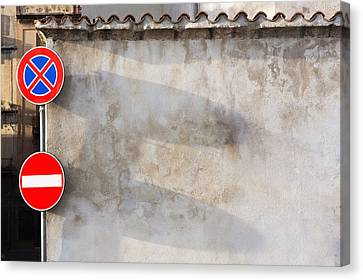 Two Traffic Signs On A Wall In The Town Canvas Print