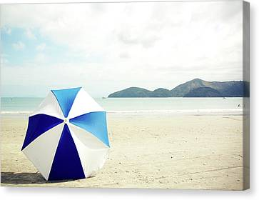 Umbrella On Sand Canvas Print by Grace Oda