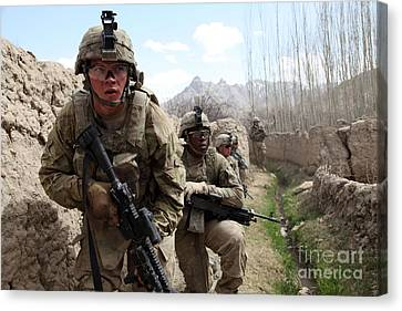 U.s. Army Platoon Moves In Behind Mud Canvas Print