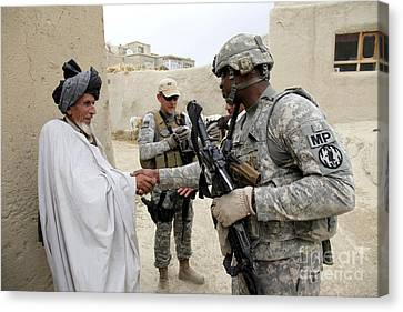 U.s. Army Soldier Shakes Hands With An Canvas Print by Stocktrek Images