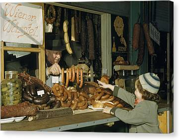 Vendor Holds Up Sausages For Young Girl Canvas Print by Volkmar Wentzel