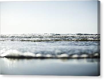 Waves Washing Into A Beach Canvas Print by Steven Errico