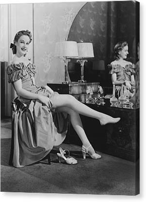 Woman Sitting At Vanity Table, Putting On Stockings, (b&w), Portrait Canvas Print by George Marks