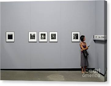 Woman Watching Photos At Exhibition Canvas Print by Sami Sarkis