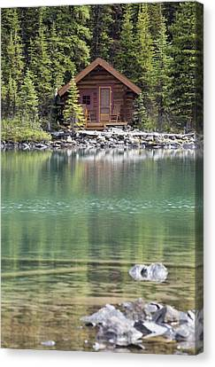 Wooden Cabin Along A Lake Shore Canvas Print by Michael Interisano