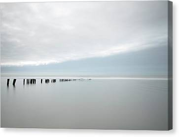 Wooden Stakes In Sea Canvas Print by Amk