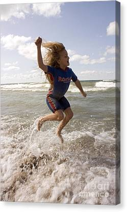 Young Girl Jumping Above Surf Canvas Print