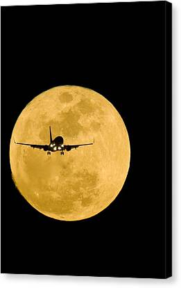 Aeroplane Silhouetted Against A Full Moon Canvas Print by David Nunuk