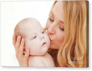 Mother Holding And Kissing Her Newborn Baby. Motherhood Canvas Print
