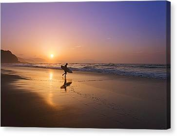 Surfer Entering Water At Sunset Canvas Print by Mikel Martinez de Osaba