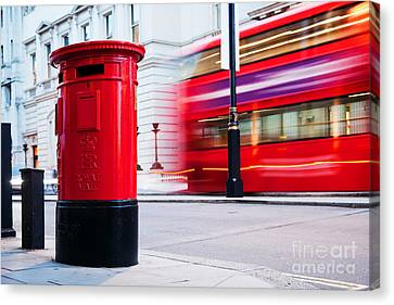 Traditional Red Mail Letter Box And Red Bus In Motion In London, The Uk Canvas Print by Michal Bednarek