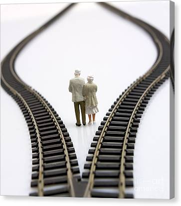 Figurines Between Two Tracks Leading Into Different Directions Symbolic Image For Making Decisions. Canvas Print by Bernard Jaubert
