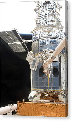 Astronauts Working On The Hubble Space Canvas Print by Stocktrek Images
