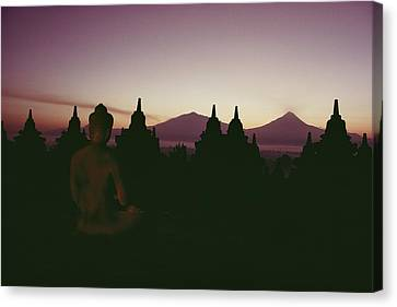 A Buddha Sits In The Canvas Print by Dean Conger