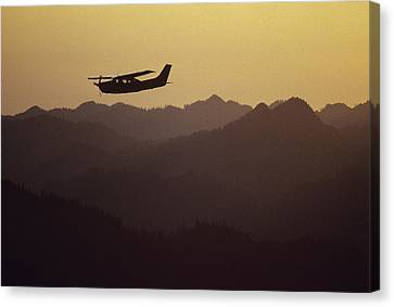 A Cessna 210 Soars Above Olympic Canvas Print by Joel Sartore