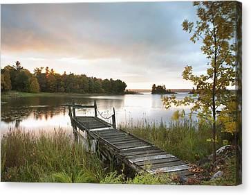A Dock On A Lake At Sunrise Near Wawa Canvas Print by Susan Dykstra