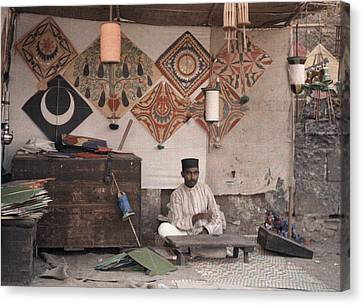 A Kite Merchant Sits In His Store Canvas Print by Gervais Courtellemont