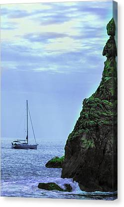 A Lone Sailboat Floats On A Calm Sea Canvas Print by George Westermak