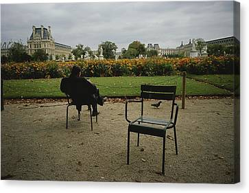 A Man Reads In The Tuileries Gardens Canvas Print by Raul Touzon