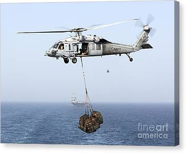 A Mh-60 Helicopter Transfers Cargo Canvas Print by Gert Kromhout