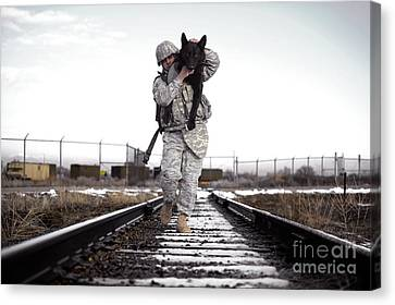 On The Move Canvas Print - A Military Dog Handler Uses An by Stocktrek Images