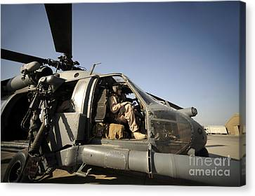 A Pilot Sits In The Cockpit Of A Hh-60g Canvas Print by Stocktrek Images