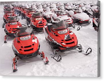 A Row Of Snowmobiles Sit Waiting Canvas Print by Taylor S. Kennedy