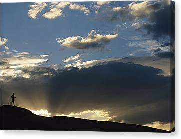 A Silhouetted Figure Trail Running Canvas Print by Bobby Model