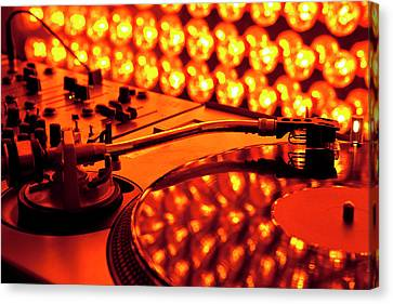 A Turntable And Sound Mixer Illuminated By Lighting Equipment Canvas Print by Twins