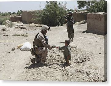 A U.s. Marine Gives Candy To An Afghan Canvas Print by Stocktrek Images